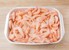 Frozen shrimps in ice. Many royal shrimps on an iron tray Royalty Free Stock Photos