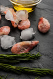 Frozen shrimps  with rosemary and olive oil on the black stone table. Some frozen shrimps with piece of ice rosemary  sprig and olive oil on the black stone Royalty Free Stock Photography