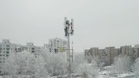 Cell tower in city. Frozen snow covered cell tower in city block, aerial video orbit stock footage