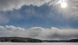 Beautiful blue sky between thick snow clouds in Haliburton Ontario. A frozen snow covered lake in Haliburton with sun bouncing off low dense clouds and a frozen stock photos