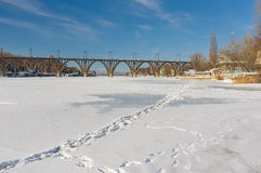 Frozen and snow covered river Dnepr with footprints in the central part of the Ukrainian city. Dnepropetrovsk, Ukraine - February 02, 2014: Frozen and snow royalty free stock images