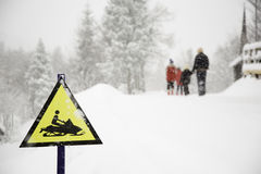 Frozen snowmobile sign and fogy, snowy background with walking family Royalty Free Stock Images