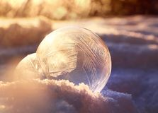 Frozen soap bubble ball against golden winter light. Magic of winter, frozen soap bubble ball on cold winter snow, crystal formations, sunlit background stock photos