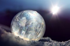 Frozen soap bubble ball on winter snow. Frozen soap bubble ball on cold winter snow, crystal formations, against bright sunlight royalty free stock image