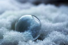 Frozen soap bubble with ice flowers in the snow, macro still lif. E with copy space, selected focus Stock Images