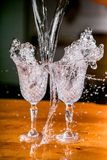 Frozen splashes in two beautiful wine glasses on a table against a dark background royalty free stock photo
