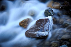 Frozen stone in run of mountain river Stock Images