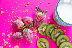 Bright breakfast picture - cereals, blue glass of cow milk and fruits at fuchsia table stock photo