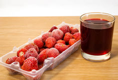 Frozen strawberries and juice. Are on the table Stock Image
