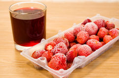 Frozen strawberries and juice. Are on the table Stock Images