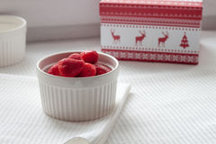 Frozen strawberries in a white plate on a white tablecloth near Christmas box Stock Photo