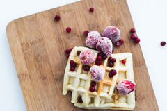 Frozen strawberry and waffles. Strawberry and cowberry. Waffles with red frozen strawberry on a wooden breadboard. Red, white, beige colours Stock Photography
