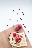 Frozen strawberry and waffles with cowberry. Strawberry and cowberry. Waffles with red frozen strawberry on a wooden breadboard. Red, white, beige colours Royalty Free Stock Photo