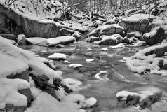 Frozen stream bed on a snowy winter day Stock Images