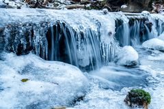 Frozen stream little waterfall with moss royalty free stock photography