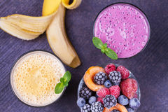 Frozen summer berries and banana milkshake garnished with mint. View from above, top studio shot. Royalty Free Stock Photo