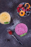 Frozen summer berries and banana milkshake garnished with mint. View from above, top studio shot. Royalty Free Stock Images