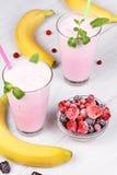 Frozen summer berries milkshakes. On white wooden background stock images