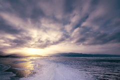 Frozen surface of Baikal lake at sunset. Royalty Free Stock Images
