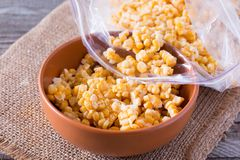 Frozen sweet corn in a bowl on a wooden table Stock Images