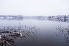 Frozen thawing lake in snow landscape Stock Images
