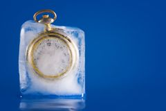 Frozen in Time 2. Pocket watch still frozen in a block of ice. The ice is beginning to melt and the clock face is becoming more visible. Image two in a series of stock photo
