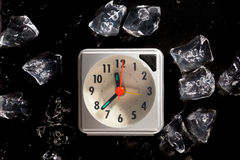 Frozen in time concept with ice cubes and a clock. And melting water drops on a dark background stock photo