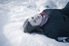Frozen to death. Concept. Young female model lying on snow Royalty Free Stock Image