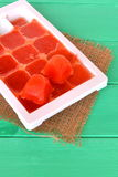 Frozen tomato juice cubes in a plastic form. Life hack, easy way to store vegetables Stock Photos
