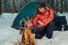 Frozen tourist warms his hands near the fire in a tent camp in t. He winter forest Stock Image