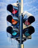Frozen traffic light. Traffic light covered with snow and ice with blue sky and clouds in the background stock images