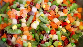 Frozen vegetable mix on frying pan stock video footage