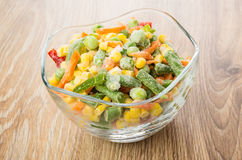 Frozen vegetable mix in glass transparent bowl on table. Frozen vegetable mix in glass transparent bowl on wooden table Stock Images