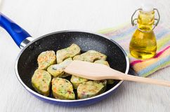 Frozen vegetable nuggets, spatula in frying pan, bottle of oil. Frozen vegetable nuggets, spatula in frying pan, bottle of vegetable oil on napkin on wooden Royalty Free Stock Images