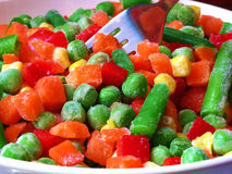 Frozen vegetables. And chopped on a plate with a fork Stock Photos
