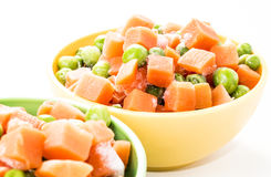 Frozen vegetables. Close-up of a frozen vegetables mix in colorful kitchen bowls isolated on white Royalty Free Stock Photography