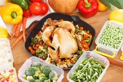 Frozen vegetables and fried chicken food. Frozen vegetables in plastic containers, fried chicken in pan. Healthy freezer food and meals Stock Photo