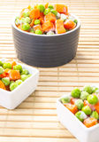 Frozen vegetables mix. In little kitchen bowls on a bamboo support Stock Images