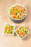 Frozen vegetables mix. In little kitchen bowls on a wooden board Royalty Free Stock Photos