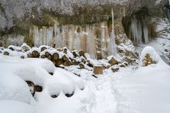 Frozen Water Columns On A Rock Wall, With Wooden Logs Cut To Size And Covered In Fresh Snow Stock Images