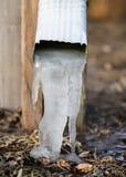 Frozen water in the drain spout. Winter hazards freezing water Stock Photo