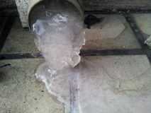Frozen water flowing from drain or sanitary pipe in winter seaso. N: A photo for icy background Stock Photo