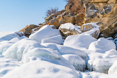 Frozen water and rocks covered with snow Stock Image