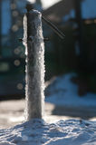 Frozen water-tap on ice rock. Frozen water production crane. Siberian frost Icy street tap for water. street residents can not use water intake Royalty Free Stock Photography