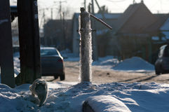 Frozen water-tap on ice rock. Frozen water production crane. Siberian frost Icy street tap for water. street residents can not use water intake Royalty Free Stock Images
