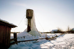 Frozen water tower with big icicles on farm Royalty Free Stock Photo