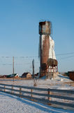 Frozen water tower. Icy water tower, an accident on the water tower, the old rusty tower with frozen water Stock Image