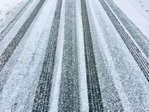 Car tyre tracks on a frozen ice tarmac road. Frozen water turns into ice on a tarmac road over which cars have driven leaving behind fresh tyre tracks in the Royalty Free Stock Photos