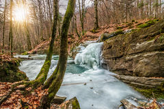 Frozen waterfall abow the huge boulder in empty forest Stock Photos