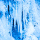 Frozen waterfall of blue icicles stock images